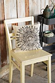Linen cushion with ornamental pattern on cream kitchen chair next to partially visible tool trolley against board wall