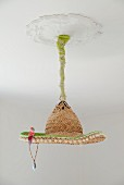 Pendant lamp with lampshade improvised from straw sombrero and bird ornament suspended from white stucco ceiling rose