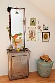 Branch of flowering quince in glass vase on antique metal cabinet in front of mirror with romantic decorations and next to gallery of pictures above African laundry basket