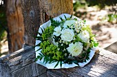 Summery bouquet with white roses (roses, dahlias, chamomile, lady's mantle) on rust wooden balustrade