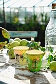 Bemalte Bechern, Apfelzweig und und Vintage Limonadenflasche auf rustikalem Tisch im Garten