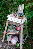 Plants in white crate on rustic side table above nostalgic pots, some planted, on old wooden crate in garden