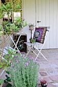 Gepflastertes Terassenplätzchen vor weißem Gartenhaus mit Lorbeer und Lavendel, im Hintergrund alte Klappstühle mit orientalischem Kissen um Tisch