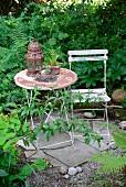 Alte Metalllaterne und Blumentopf auf Gartentisch mit Rost-Patina und schabloniertem Blumendekor, auf Boden mit Bruchsteinplatten und Kies