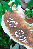 Potted house leeks on rusty old garden table with stencilled floral motifs