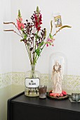 Summer flowers in shades of red in vintage apothecary jar next to figurine of the Madonna decorated with pink flowers under glass cover on black sideboard