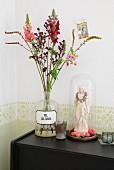 Sommerblumen in Rottönen in Vintage Apothekerflasche, daneben Madonnenfigur dekoriert mit pinkfarbenen Blüten unter Glashaube auf schwarzem Sideboard