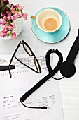 Designer spectacles and telephone handset on company stationary next to gold-rimmed cup