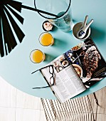 Open cookbook, glasses of juice and palm frond on ice-blue tabletop