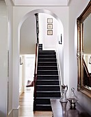 Staircase in hallway with elegant cloakroom mirror and antique glass carafes on chest of drawers
