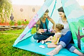 Young couple and toddler daughter having a tea party in tent