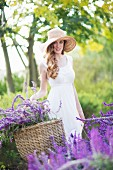 Portrait of beautiful young woman in meadow carrying basket of purple flowers