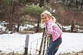 Young girl climbing wire fence in field