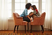 Young female couple sitting head to head in two armchairs pushed together