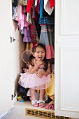 Girl in princess costume hiding in wardrobe