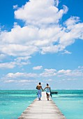 Young couple walking on pier, San Pedro, Belize