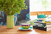 Teacup next to teapot on stack of books and ceramic jug of lady's mantle