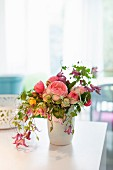 Bouquet of fragrant English roses, clematis and other flowers in white vase on table