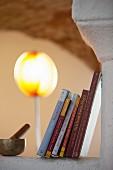 Bücherstapel und Klangschale mit Klöppel auf gemauerter Ablage, im Hintergrund Stehleuchte