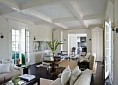 Langgestreckter, hell möblierter Wohnraum mit Kassettendecke und beidseitiger Belichtung durch Fenstertüren