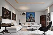 White living room in eclectic mixture of antique and modern elements; antique floral still-life paintings and modern oil painting on walls