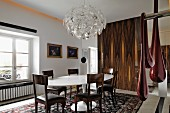 Bright dining room with white designer dining chairs, gilt-framed oil paintings and modern artworks