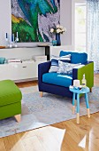 A comfortable patchwork armchair in blue and green on a rug with a side table and a foot stool with a green cover