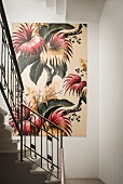 Large, floral artwork on white wall in stairwell with Art Nouveau metal balustrade
