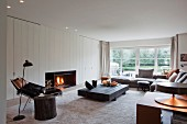 Modern interior in Scandinavian style - comfortable lounge with open fire, low coffee table made from dark wood, corner sofa and reading chair below black standard lamp in foreground