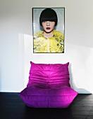 Purple beanbag on dark wooden floor below framed photo of woman on wall