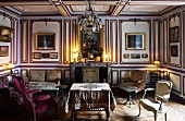 Wood-panelled parlour with gallery of paintings and collection of antique armchairs