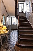 Foyer in historical house with lamp on console table and staircase