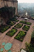 Terrace garden with rectangular beds, gravel paths and view of historical town in morning mist