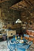 Himmelblau lackierter Bistrotisch mit Gartenstühlen und antiker, französischer Pendelleuchte in historischem Stallgebäude