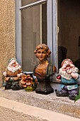 French garden gnomes and antique bust of woman on windowsill of historical building