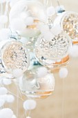 Silberfarbene Weihnachtskugeln und kleine, weisse Flauschkugeln als Schneeflocken-Deko