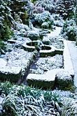 Winterlich beschneite Gartenlandschaft mit geometrisch angelegten Heckenstrukturen