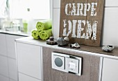 Detail of a built-in radio set in a light brown wall tile with stones and a 'Carpe Diem' sign on the shelf above