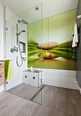 Effektvolle Rückwand aus Glas mit Naturmotiv in bodenebenem Duschbereich, Glastrennwand als Spritzschutz, hellbraun marmorierte Bodenfliesen