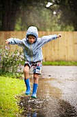 Boy in wellington boots jumping in puddle