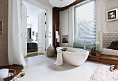 A free-standing, limestone bathtub and an artificial leather armchair in a white, cosy bathroom with built-in teak units and a view through a frame and panel door into the adjoining bedroom