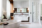 Harmonious material mix in a spa bathroom – an oval bathtub, two console basins and a wall with a woven relief effect in limestone combined with built-in teak units