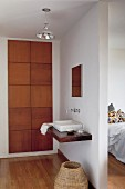 Washing area - washstand and wall-mounted taps on partition wall and fitted cupboard with solid wooden doors to one side