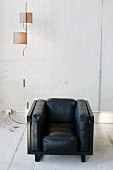 Black, cubic leather armchair and designer pendant lamp with cylindrical lampshades against exposed concrete wall