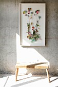 Various flowers in display case on exposed concrete wall above rustic wooden stool in shaft of sunlight on floor