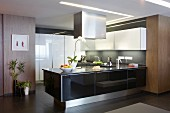 Designer kitchen in mixture of materials - counter with glossy black front below stainless steel extractor hood and white overhead cabinets on grey wall
