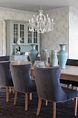 Gepolsterte Stühle mit blauem Samtbezug an langer Tafel aus hellem Holz, darauf Vasensammlung, Kronleuchter mit Kristallschmuck in traditionellem Ambiente