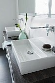 A square console basin with wall taps on a wooden washstand with drawers