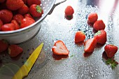 Freshly washed strawberries in a colander on a wet, stainless steel work surface