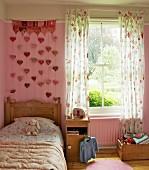 Mädchenzimmer im romantischen Landhausstil mit Blümchendeko auf Bettbezug und Vorhang; Wandbehang mit Herzchen an pinkfarbener Wand